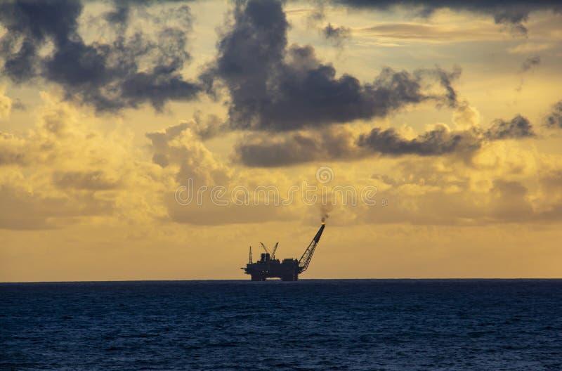 工作面积近海处在公海、石油工业和美好的天和日落 免版税库存照片