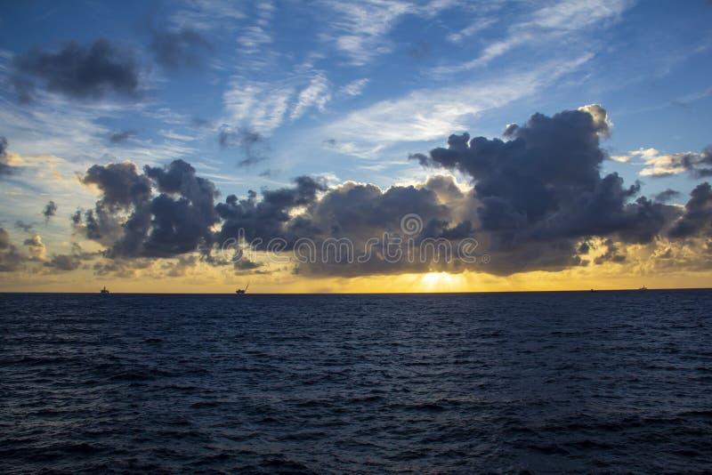 工作面积近海处在公海、石油工业和美好的天和日落 图库摄影