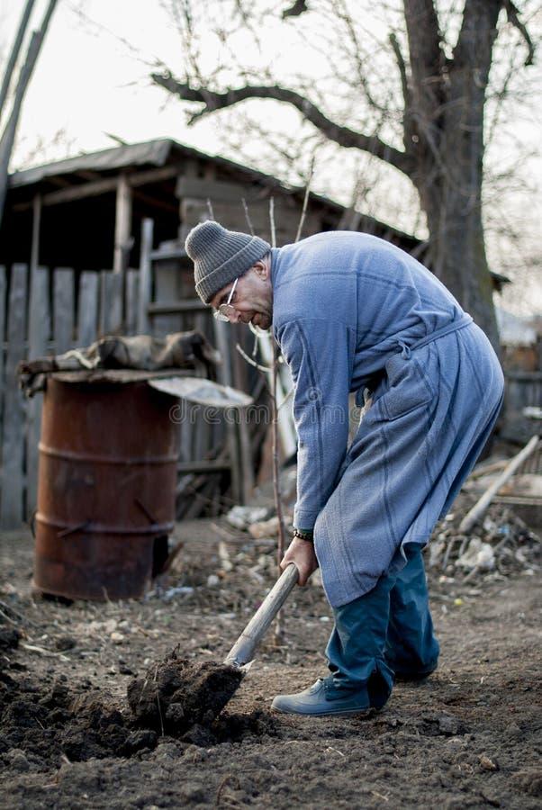 工作他的土地用一个传统方式的可怜和老罗马尼亚人用空的手 免版税库存图片