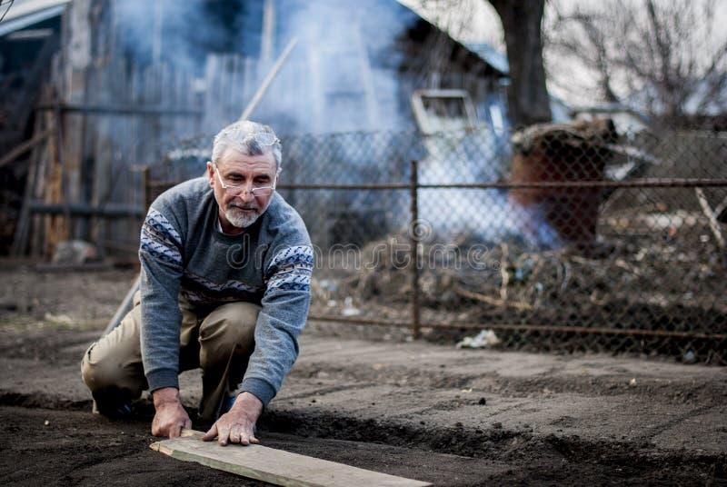 工作他的土地用一个传统方式的老罗马尼亚人用空的手 免版税库存图片
