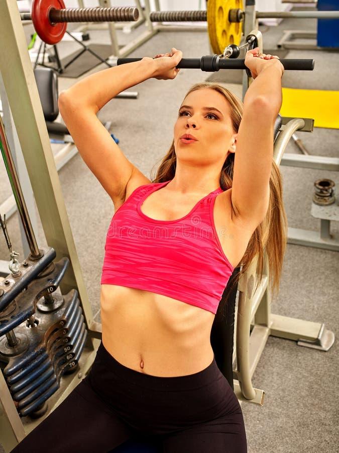 工作他的胳膊和胸口的妇女在健身房 库存照片
