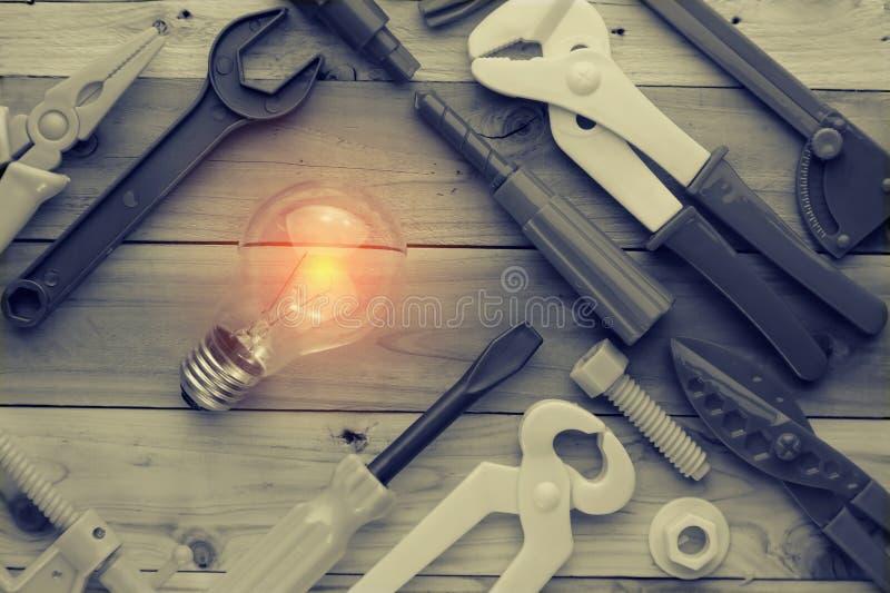 工具和仪器戏弄与在木纹理的电灯泡 免版税库存图片