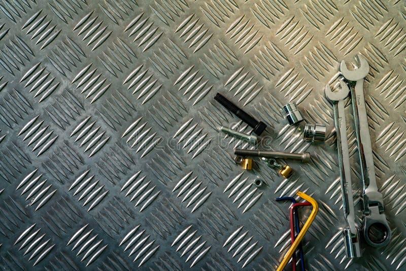 工具顶视图在工业金属验查员板材的 反滑行的金属checkerplate 坚果、螺栓和十六进制键在金属板 免版税库存照片