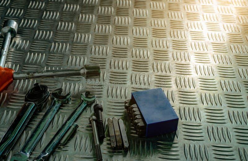 工具顶视图在工业金属验查员板材的 反滑行的金属checkerplate 坚果、螺栓和十六进制键在金属板 库存照片