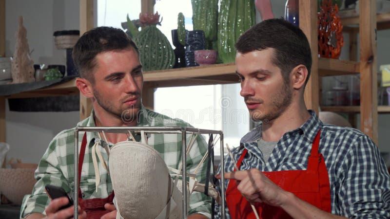 工匠和他的使用巧妙的电话的学生,当装饰陶瓷雕象时 免版税库存照片