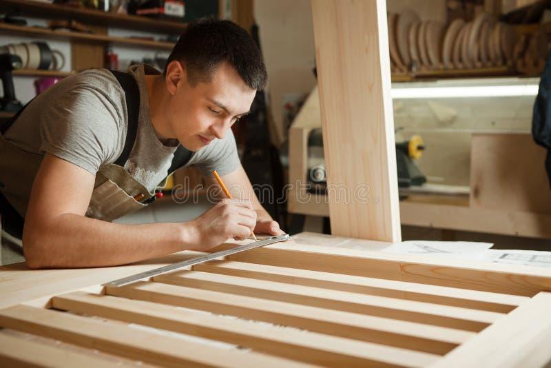 工匠木板条之间的措施距离在统治者帮助下  库存图片