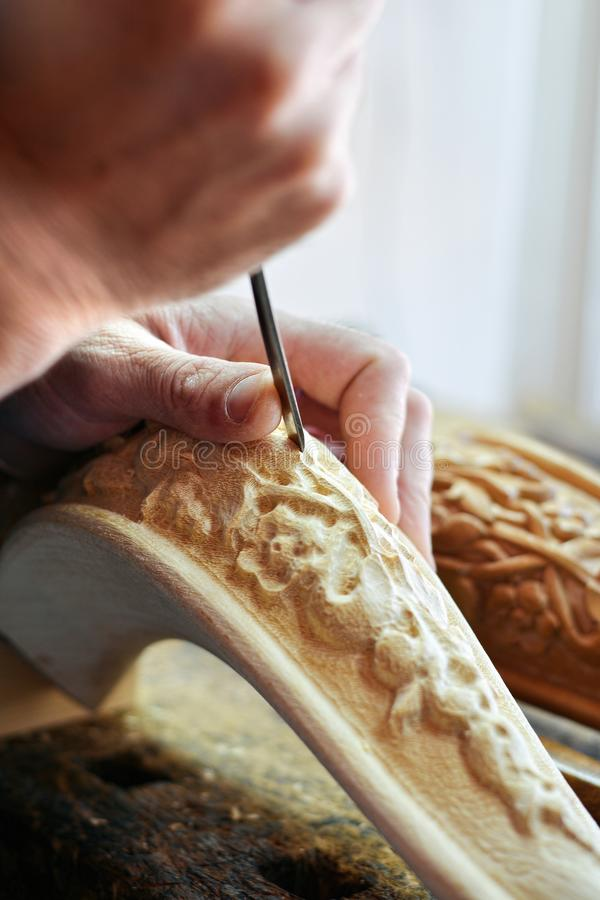 工匠木雕家创造一件家具装饰品 木雕家` s手,凿子,工具,木头雕刻了一部分的一把经典样式椅子 库存照片