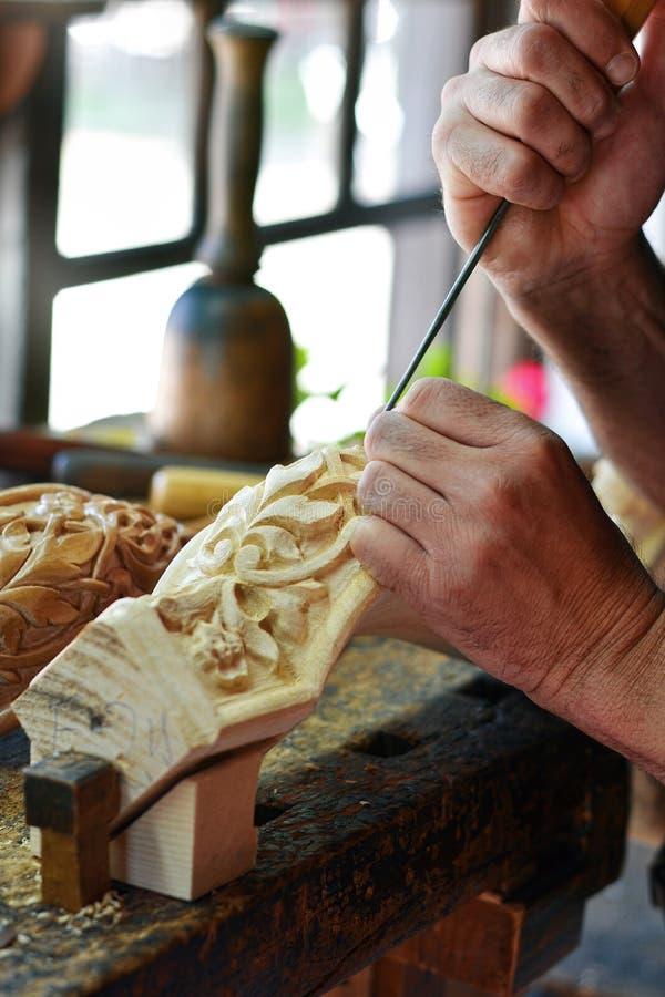 工匠木雕家创造一件家具装饰品 木雕家` s手,凿子,工具,木头雕刻了一部分的一把经典样式椅子 免版税库存照片