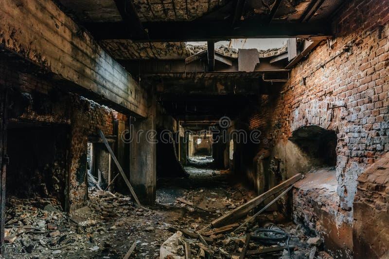 工厂厂房内部废墟在灾害以后的或战争或者地震 黑暗的蠕动的隧道或走廊,恐怖大气 免版税库存图片