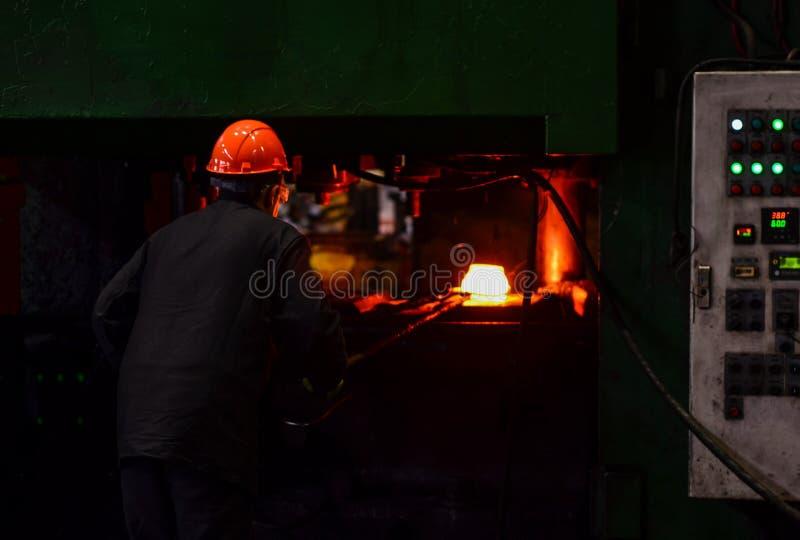工厂焊接特写镜头的产业工人 在smeltery的热的铁由工作者举行了 免版税图库摄影