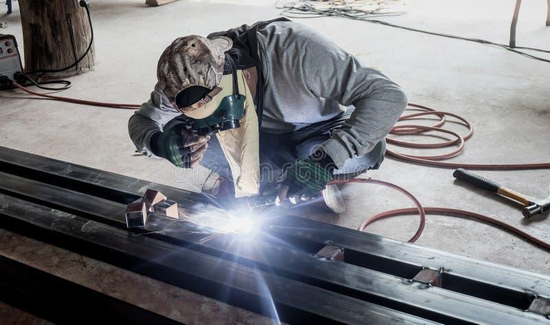 工厂焊接的特写镜头的产业工人 研在钢结构的电轮子在工厂 库存图片