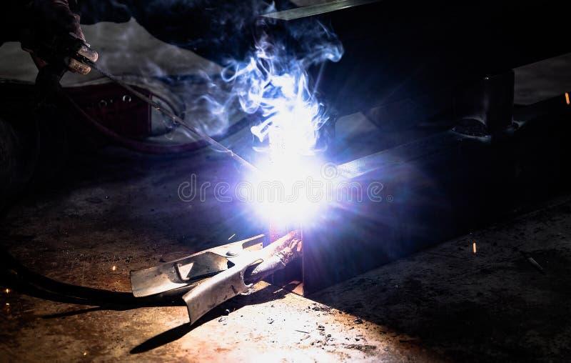 工厂焊接的特写镜头的产业工人 研在钢结构的电轮子在工厂 免版税库存图片