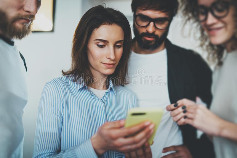 工友业务会议概念 握流动智能手机手和显示信息的少妇对她的同事 免版税库存照片