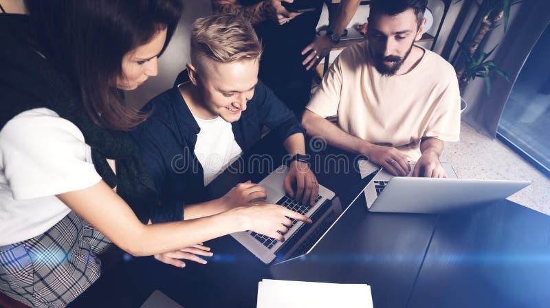工友合作在工作 小组在创造性的办公室的时髦便衣的年轻商人 库存照片