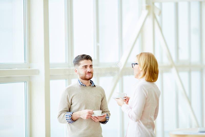 工友用有的咖啡谈话 免版税库存照片