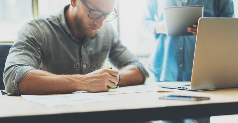 工友队激发灵感过程在现代顶楼 戴眼镜,人的项目负责人做笔记标志 创造性 库存图片