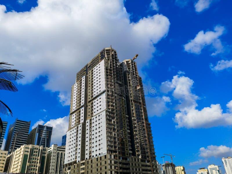 工地工作、起重机和大厦建设中反对蓝色多云天空 免版税库存图片
