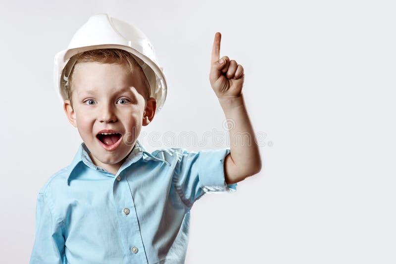 工头的浅兰的衬衣和建筑盔甲的男孩举手指,好象他找到想法 库存图片