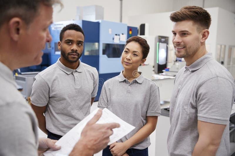 工程学在繁忙的车间工厂地板上的队会议  免版税库存图片