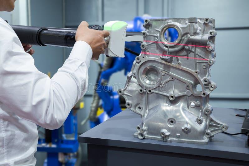 工程师与3D便携式的测量的扫描汽车零件一起使用 图库摄影