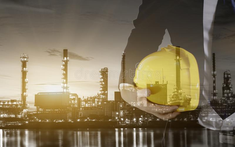 工程师两次曝光有安全黄色盔甲的工作者安全和黑白炼油厂产业植物的 免版税库存照片