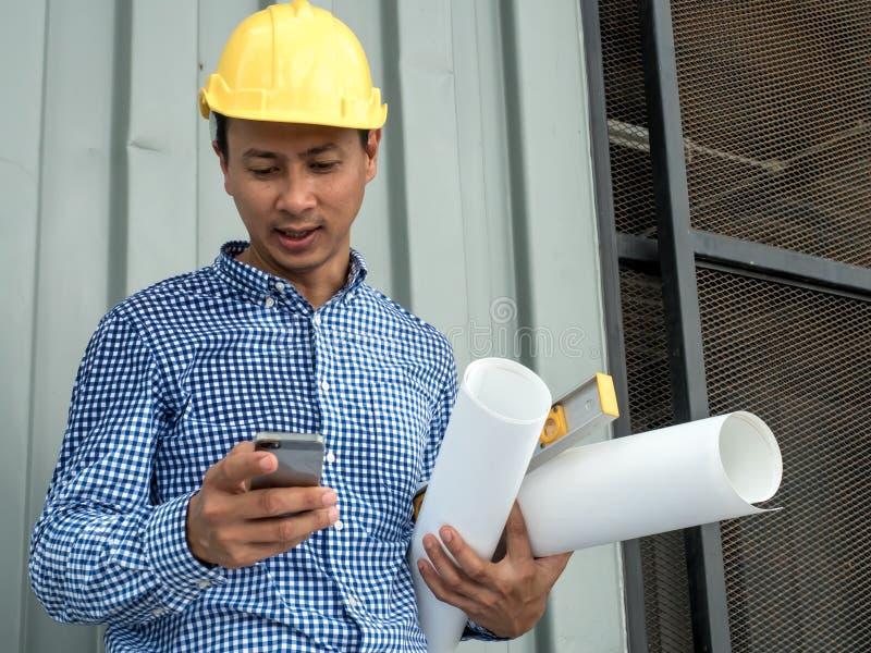 工程师举行晒图纸结构图计划和拿着手机,工作在办公室,工程学工具的建筑师  库存图片
