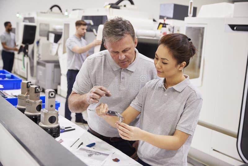 工程师和女性学徒测量的组分在工厂 库存照片