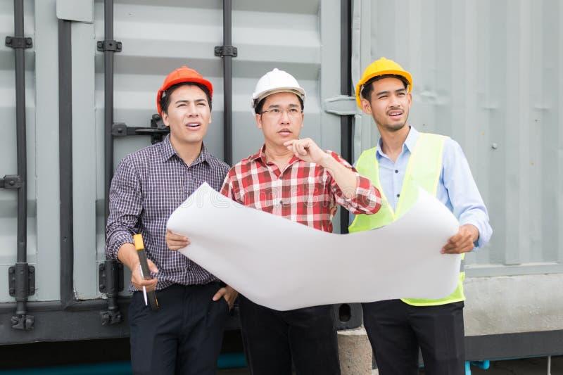 工程师和建筑在手边合作佩带的安全帽和图纸 他们是可循环材料和建筑过程 免版税库存照片