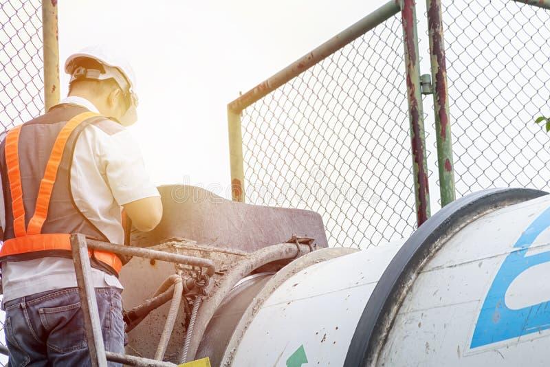 工程师回顾一辆大水泥搅拌车 建筑,不动产工作要求关心的专家 站立在混合 免版税库存图片