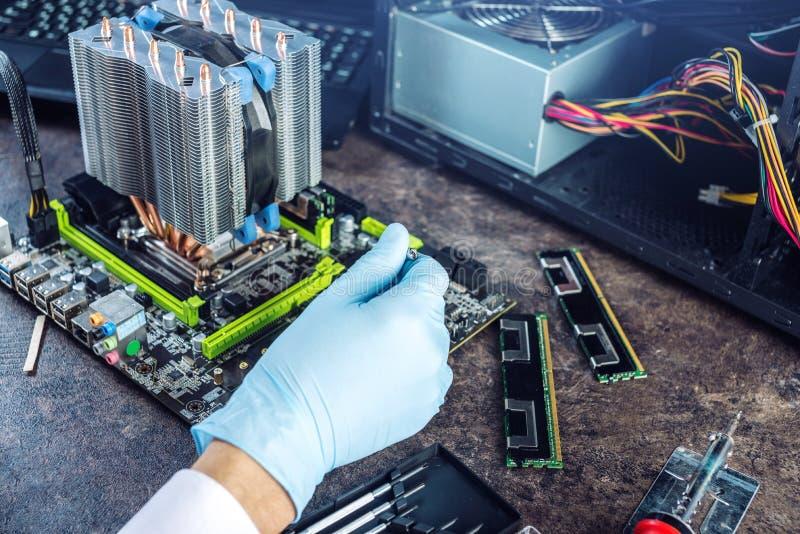 工程师在手套的技术员计算机在手上回顾失败 修理微集成电路的概念 免版税库存图片