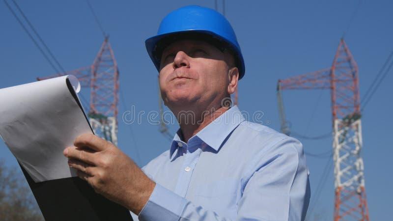 工程师在早餐时间的电工工作在议程吃并且读了 免版税库存图片