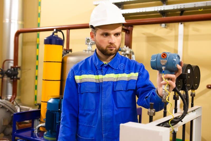 工程师在能源厂审查设备 免版税库存照片