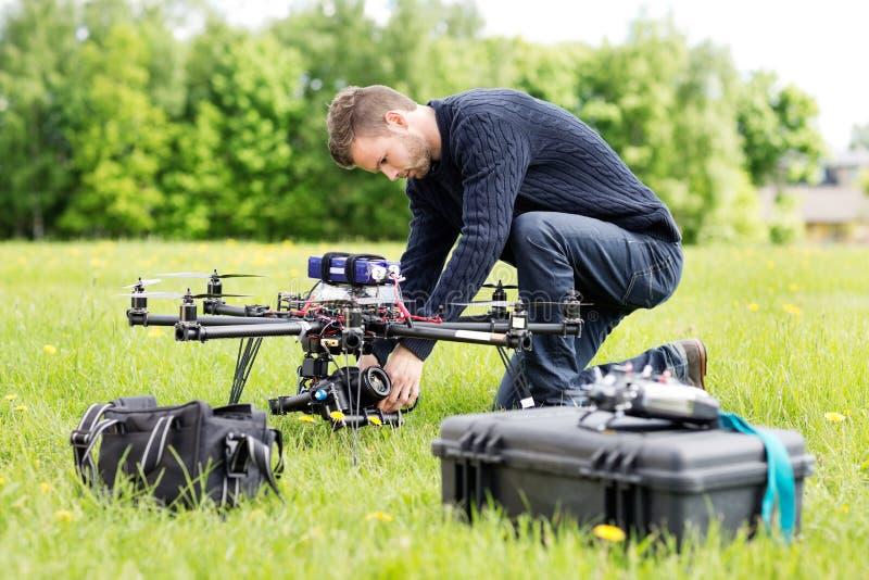 工程师在UAV直升机的设置照相机 库存照片