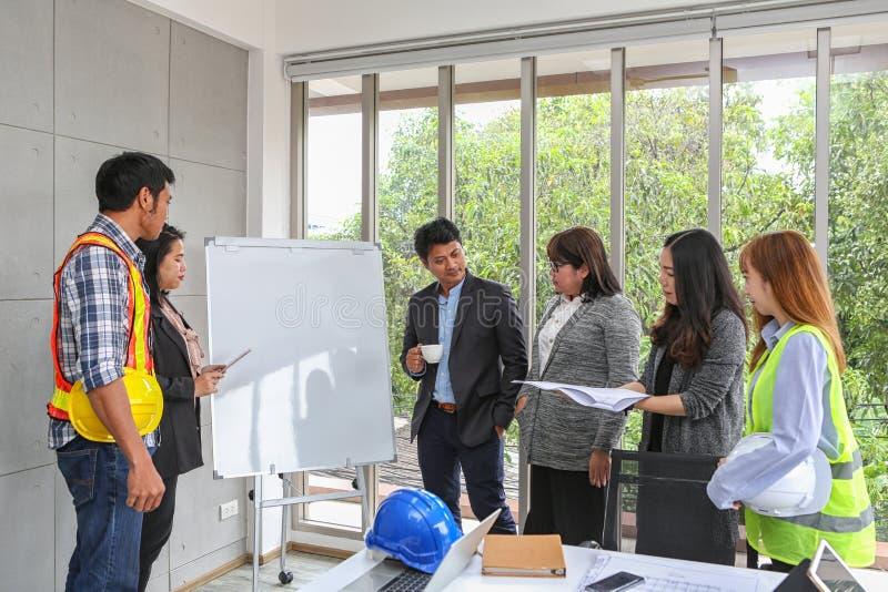 工程师在whiteboard见面 图纸室内设计结构和发展 队的承包商介绍和 库存照片
