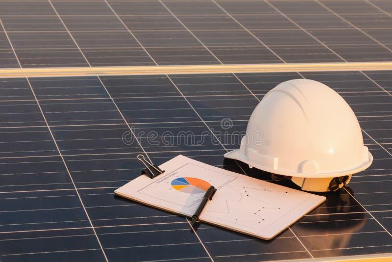 工程师帽子和图表在太阳电池板,供选择的电来源,能承受的资源的概念被安置 库存图片