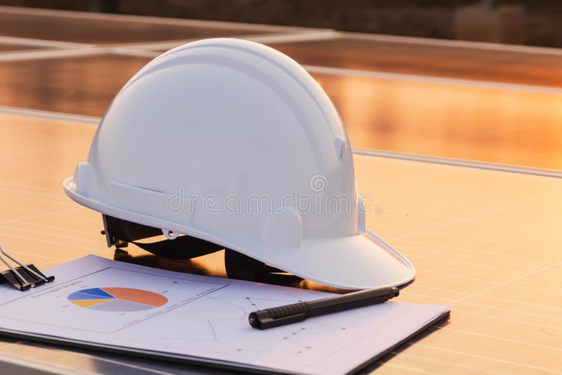 工程师帽子和图表在太阳电池板,供选择的电来源,能承受的资源的概念被安置 库存照片
