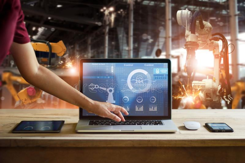 工程师感人的膝上型计算机检查和控制焊接机器人学 免版税库存照片