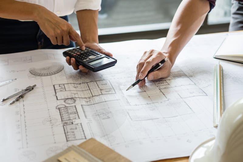 工程师或建筑师与建筑项目一起使用,画和速写的伙伴会议的图象检查的 库存照片