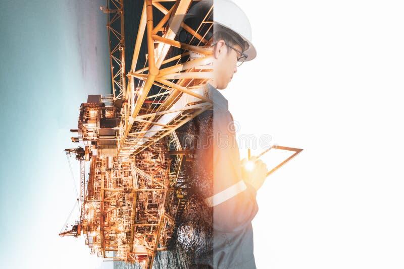 工程师或技术员人两次曝光有安全帽被管理的平台或植物的通过使用有近海油的片剂和 免版税库存照片