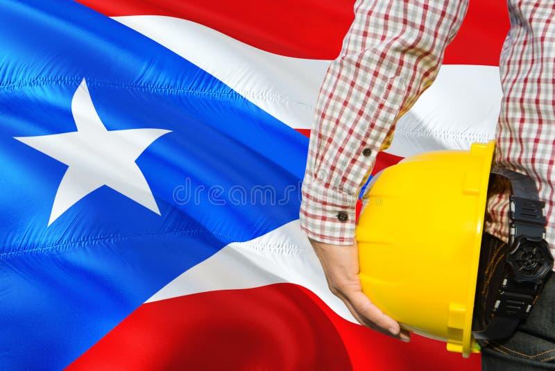 工程师拿着与挥动波多黎各旗子背景的黄色安全帽 建筑和大厦概念 库存照片