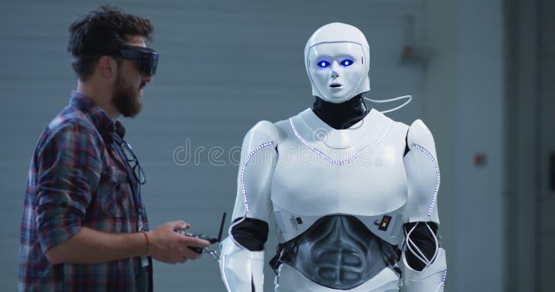 工程师控制机器人递运动 免版税库存照片