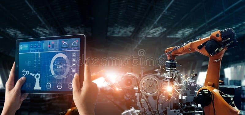 工程师检查和控制焊接的机器人学自动胳膊机器在汽车聪明的工厂 库存照片
