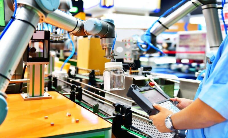 工程师检查和控制自动化机器人胳膊 免版税库存照片