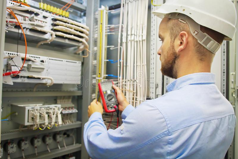 工程师电与多用电表 男性与多用电表探针的技术员审查的fusebox侧视图  免版税图库摄影