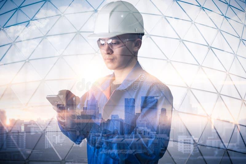 工程师的两次曝光图象使用一个智能手机的在日出期间躺在与都市风景图象 engineeri的概念 免版税库存图片
