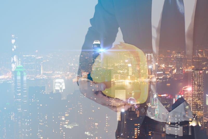 工程师的两次曝光概念有安全黄色盔甲的工作者安全的有现代城市夜背景 产业 库存照片