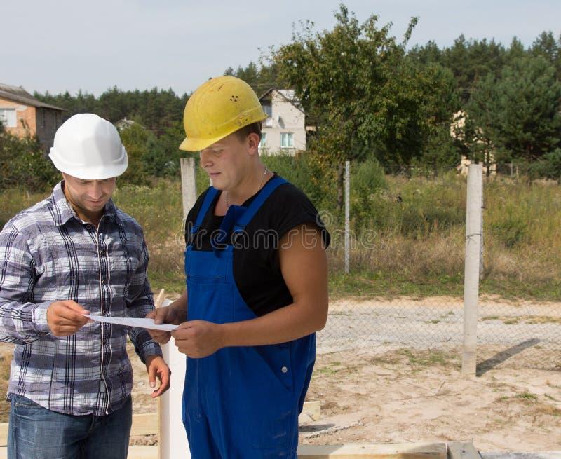 工程师谈论项目对建筑工人 免版税库存照片