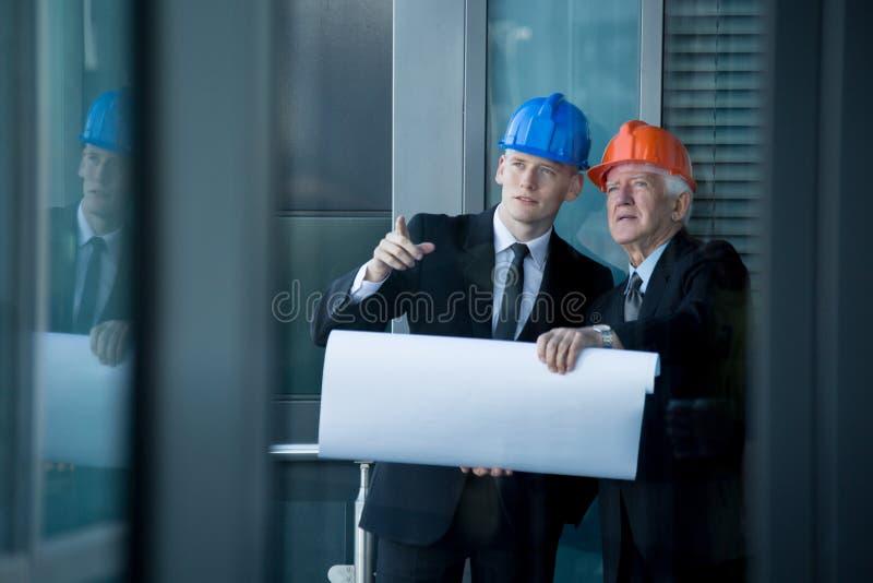 年轻工程师谈话与资深上司 免版税库存图片