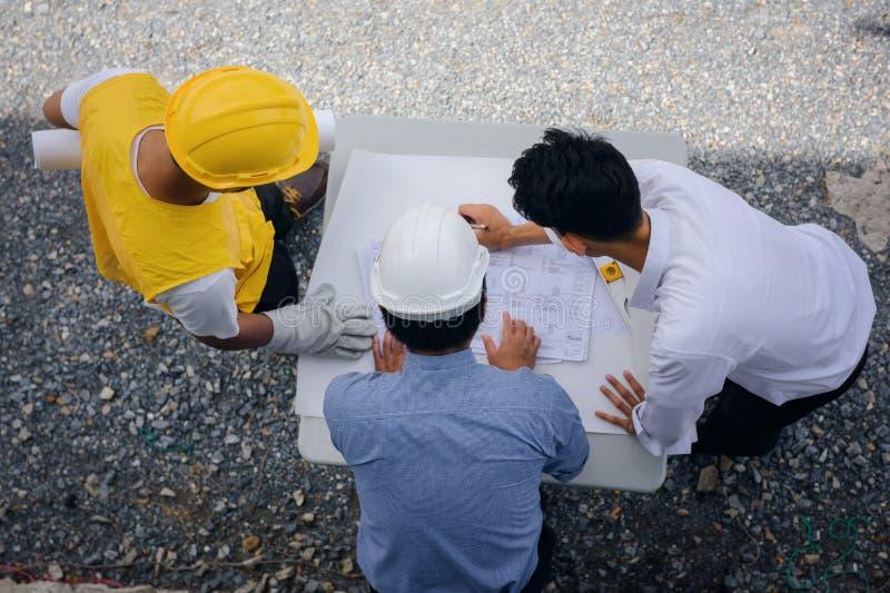 工程师队平的位置与图纸的 免版税库存照片