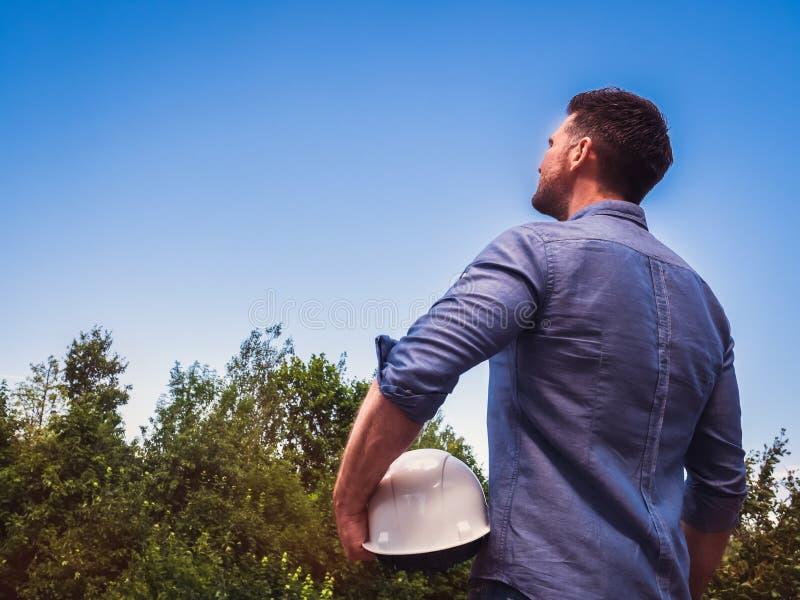 工程师,拿着白色安全帽在公园 免版税库存照片